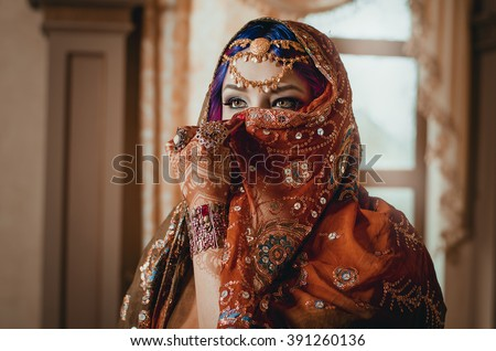 portrait of a beautiful young woman in traditional Indian ethnic dress and painted ational patterns on the hands, mehendi. girl covers her face with a handkerchief - stock photo