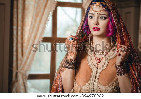 portrait of a beautiful young woman in traditional Indian ethnic dress and painted ational patterns on the hands, mehendi. - stock photo
