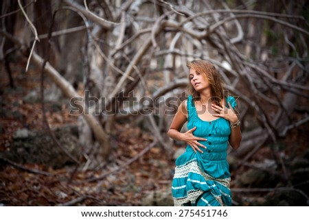 Portrait of a beautiful young woman in turquoise dress standing by trees In jungle forest - stock photo