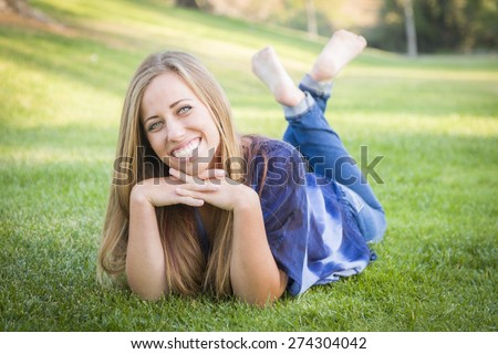 Portrait of a Beautiful Young Woman Laying in the Grass Outdoors at the Park. - stock photo