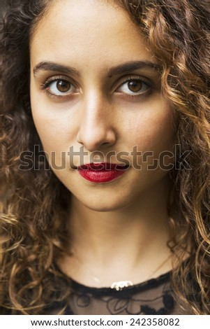 Portrait of a beautiful young woman looking into camera with red lipstick and brown eyes - stock photo