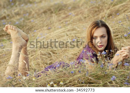 portrait of a beautiful young woman lying in a field of wheat and flowers - stock photo
