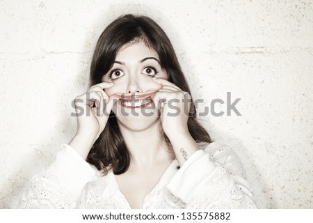 Portrait of a beautiful young woman making a goofy freak / monster face. Her big eyes wide open while her hands are stretching her mouth upwards. All in all, looking rather foolish - stock photo