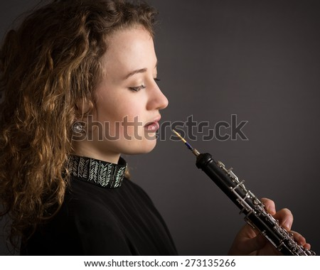 portrait of a beautiful young woman oboe player who is about to start playing a beautiful piece on her oboe and is dressed in black.