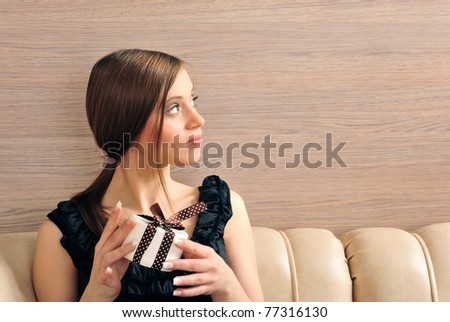 Portrait of a beautiful young woman offering a present. Office background. She is looking at right side on copyspace