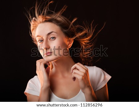 Portrait of a beautiful young woman on a dark background - stock photo