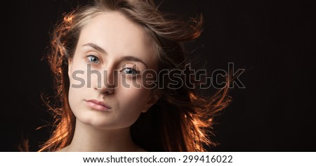 Portrait of a beautiful young woman on a dark background with copy-space
