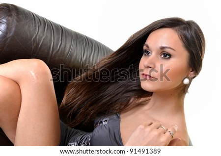Portrait of a beautiful young woman on a leather sofa isolated on white - stock photo