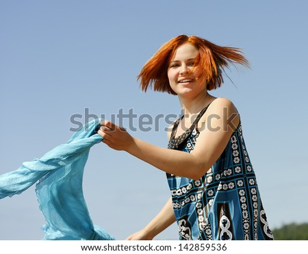Portrait of a beautiful young woman outside running on the beach with a scarf smiling - stock photo