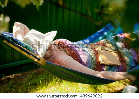 Portrait of a Beautiful Young woman relaxing by laying in hammock outdoors on a bright sunny day of spring or summer and green grass background - stock photo