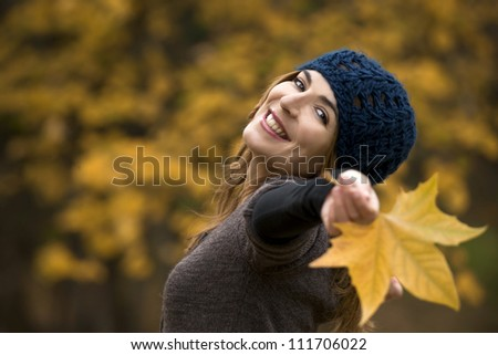 Portrait of a beautiful young woman relaxing with arms open and enjoying the fall season - stock photo