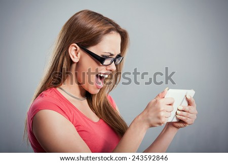 Portrait of a beautiful young woman shouting on a digital tablet. Studio Shot. - stock photo
