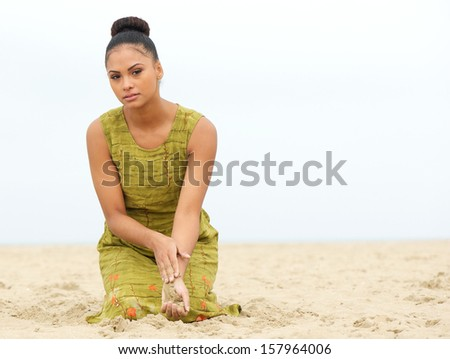 Portrait of a beautiful young woman sitting at the beach with sand flowing from hand - stock photo