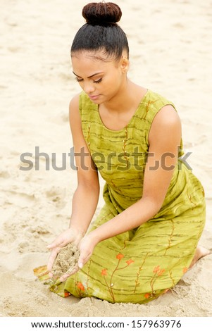 Portrait of a beautiful young woman sitting at the beach with sand flowing from hands - stock photo