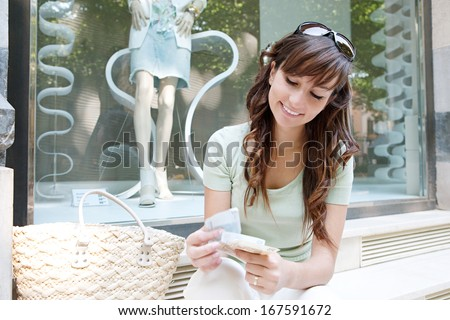 Portrait of a beautiful young woman sitting by a fashion store window display counting bank notes bills currency money during a shopping day out, smiling outdoors. - stock photo