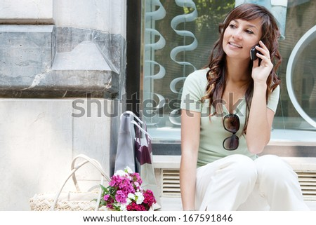 Portrait of a beautiful young woman sitting by a fashion store window display relaxing and having a phone call conversation using her smartphone during a shopping day out, smiling outdoors.