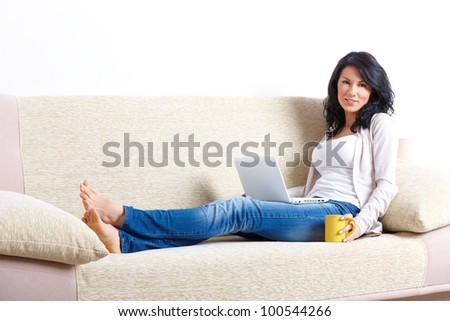 Portrait of a beautiful young woman sitting on sofa and using laptop in home - stock photo