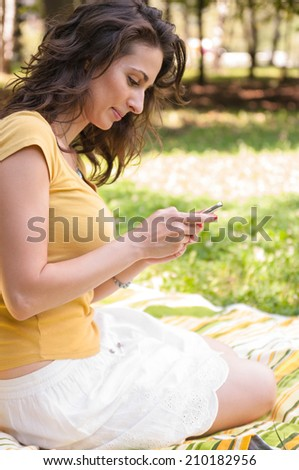 Portrait of a beautiful young woman sitting on the grass at park and chatting on phone - stock photo