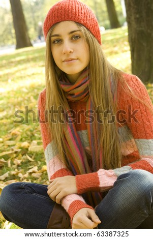 Portrait of a beautiful young woman. Sitting outside in a pile of autumn leaves, smiling - stock photo