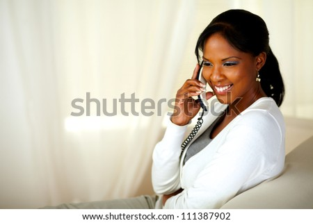 Portrait of a beautiful young woman smiling and speaking on phone. With copyspace