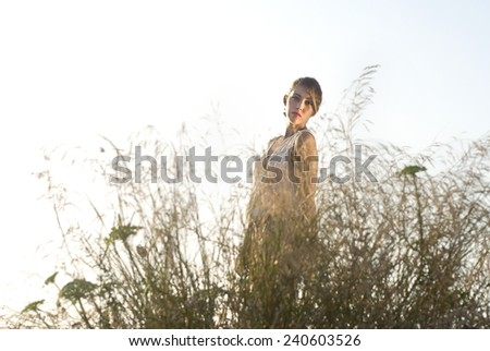 Portrait Of A Beautiful Young Woman Standing Behind Bushes - stock photo