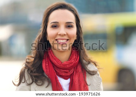 Portrait of a beautiful young woman standing in the city street. - stock photo
