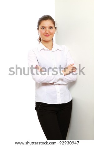 Portrait of a beautiful young woman standing near wall - stock photo