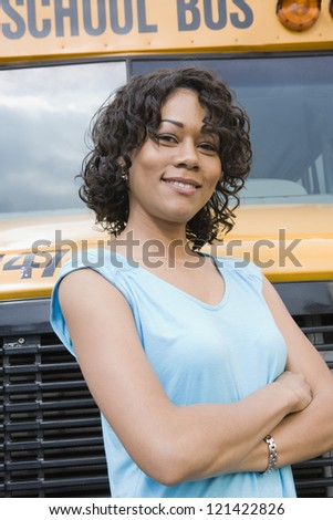 Portrait of a beautiful young woman standing with arms crossed against school bus