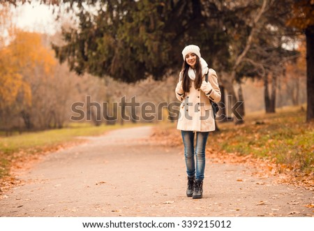 Portrait of a beautiful young woman student with a backpack while walking in the autumn park - stock photo