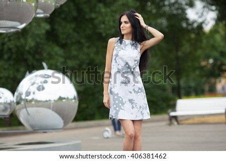 Portrait of a beautiful young woman. The model wears a summer dress. Summer shot. Outdoors - stock photo
