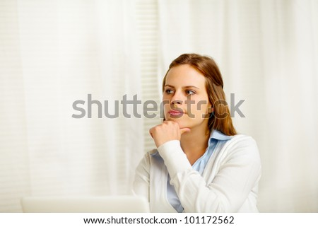 Portrait of a beautiful young woman thinking in from laptop - stock photo