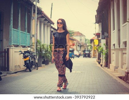 portrait of a beautiful young woman walking in the middle of the street