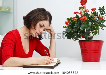 Portrait of a beautiful young woman wearing red top, sitting at home at her desk, looking down and writing, green and red flowers in red pot - stock photo