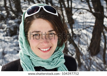 Portrait of a beautiful young woman wearing scarf and sunglasses, smiling into camera - winter forest in background - stock photo