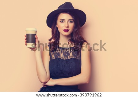 portrait of a beautiful young woman with a cup of coffee standing on the pink background - stock photo