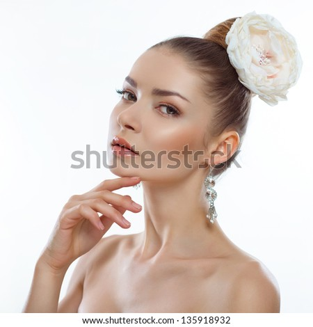 portrait of a beautiful young woman with a flower in her hair on a white background