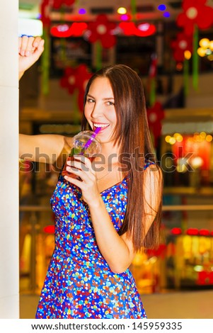 Portrait of a beautiful young woman with a glass of juice in shopping center