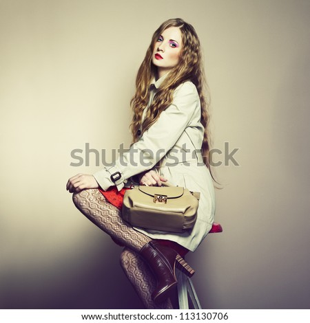 Portrait of a beautiful young woman with a handbag. Fashion photo - stock photo