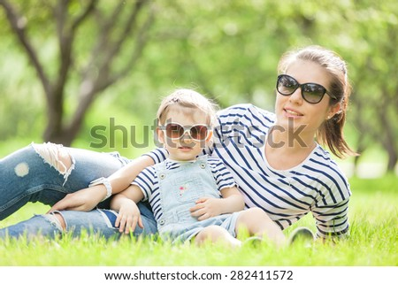 Portrait of a beautiful young woman with a small child in park