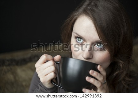 Portrait of a beautiful young woman with beautiful green eyes and brown hair holding a black coffee cup.