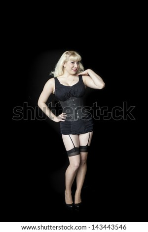 Portrait of a beautiful young woman with blond hair and brown eyes shot in a black corset.