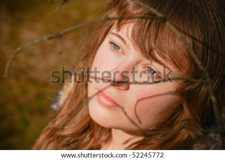 portrait of a beautiful young woman with blue eyes, she is dreaming, there are shadows from the branch on her face