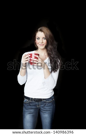 Portrait of a beautiful young woman with brown hair and blue eyes. She is on a black background and drinking coffee from a red cup. - stock photo