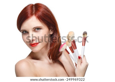 Portrait of a beautiful young woman with brushes for make-up on a white background. - stock photo