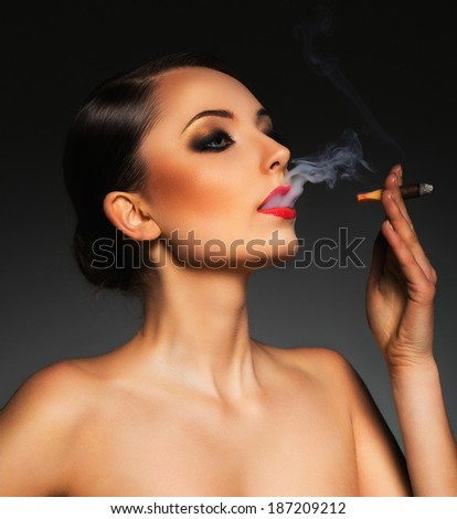 Portrait of a beautiful young woman with cigar and with a glamorous retro makeup - stock photo