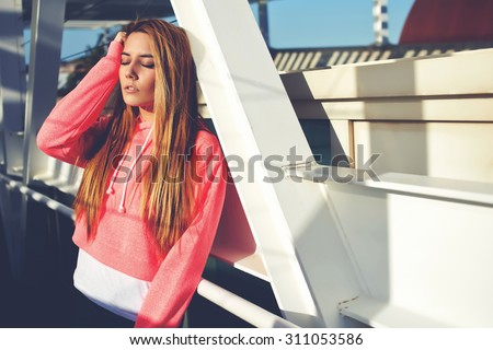 Portrait of a beautiful young woman with closed eyes enjoying sunny afternoon outdoors, stylish hipster girl resting after active walk during her free recreation time, gorgeous female relaxing outside - stock photo