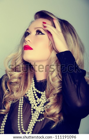 portrait of a beautiful young woman with curly blond hair and glamour make-up with red lips wearing a black blouse and pearls - stock photo