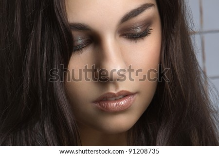 portrait of a beautiful young woman with curly brown hair, close-up - stock photo