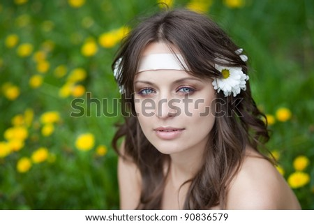 Portrait of a beautiful young woman with daisies in her hair, outdoors, park - stock photo