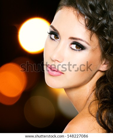 Portrait of a beautiful young woman with fashion makeup over bright night lights - stock photo